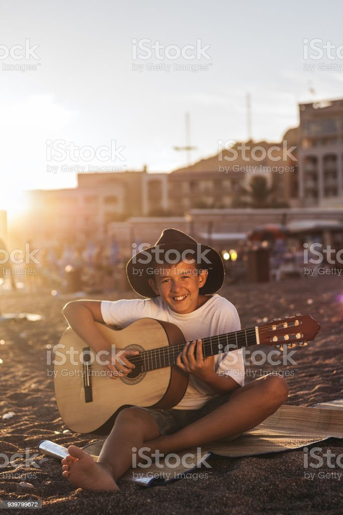 Portrait of cute boy playing a guitar on beach stock photo