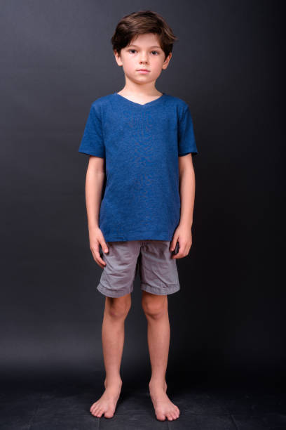 Portrait Of Cute Boy Standing Barefoot Against Black Background stock photo