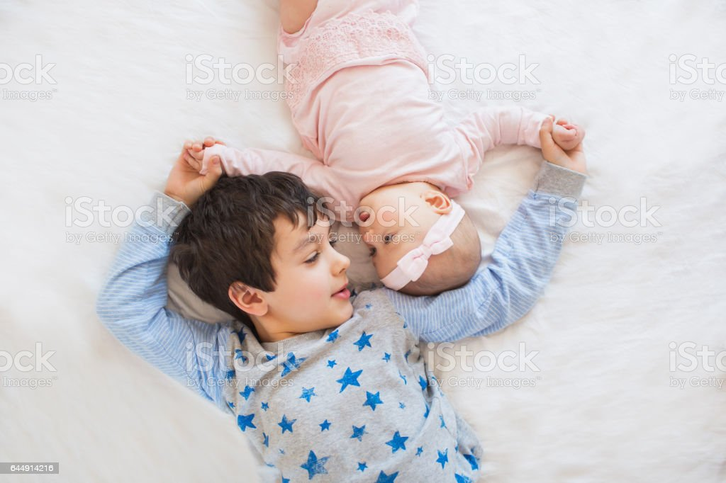 TOP VIEW: Portrait of cute brother with his little sister stock photo