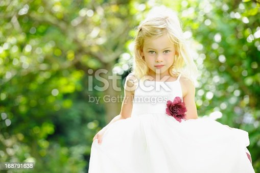 A portrait of a cute caucasian little girl/ bridesmaid/ flower girl in the garden.