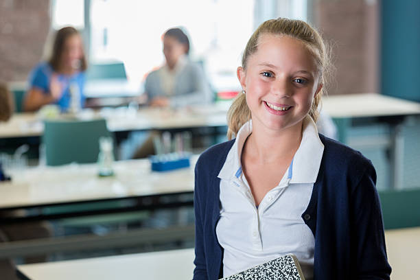 Portrait of cute Caucasian preteen in science class Portrait of a cute, blonde preteen Caucasian female student in a science classroom and holding a composition notebook. Cute blonde Caucasian preteen female posing in science class. cute middle school girls stock pictures, royalty-free photos & images
