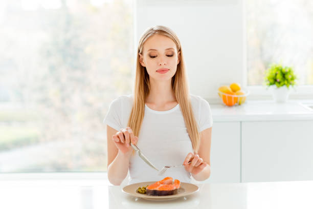 portrait of cute charming lady dieting have lunch peas protein vegetable use snacking fork knife break pause sit big kitchen wear modern cotton clothing - woman eating salmon imagens e fotografias de stock