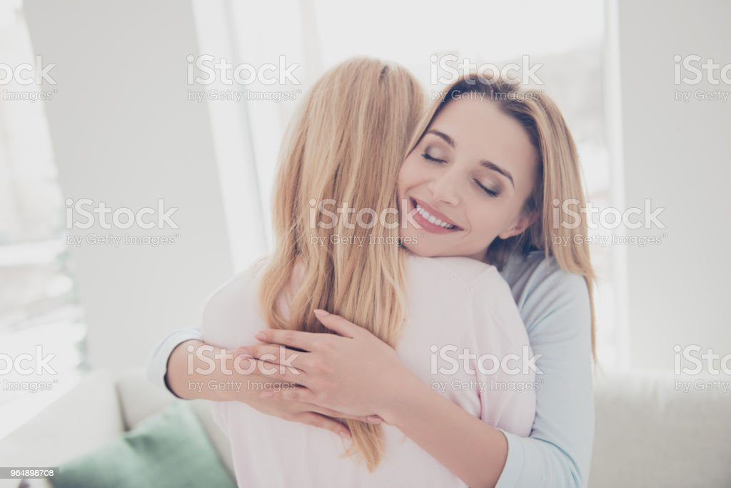 Portrait of cute charming lovely beloved sweet girl enjoying warm hugs with her mother keeping eyes closed having pleasure, my soul heart love you forever royalty-free stock photo