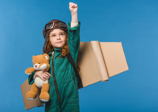portrait of cute child in pilot costume with teddy bear and handmade paper plane wings isolated on blue portrait of cute child in pilot costume with teddy bear and handmade paper plane wings isolated on blue alternative pose stock pictures, royalty-free photos & images
