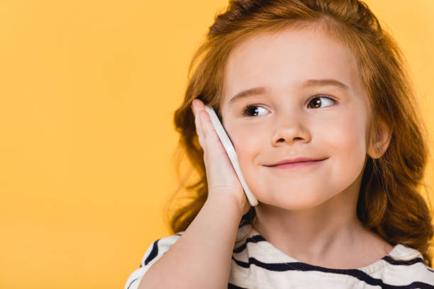 portrait of cute child talking on smartphone isolated on yellow portrait of cute child talking on smartphone isolated on yellow alternative pose stock pictures, royalty-free photos & images