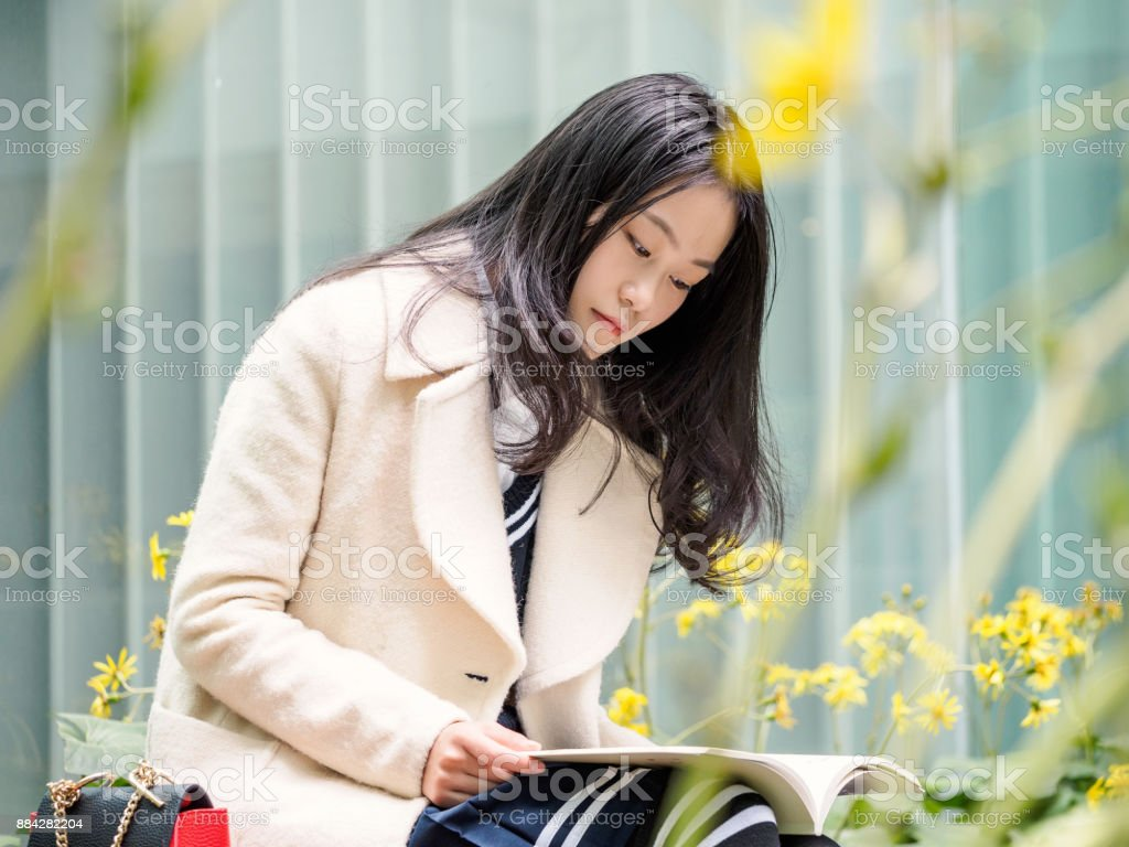 Portrait Of Cute Chinese Girl Reading Book In Campus Stock Image
