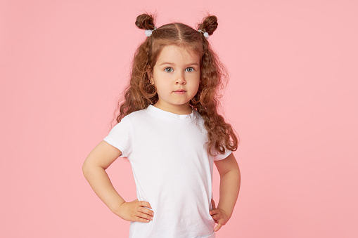 Portrait of cute european little toddler girl over pink background. Looking at camera. Child model in white T-shirt. Advertising childrens products