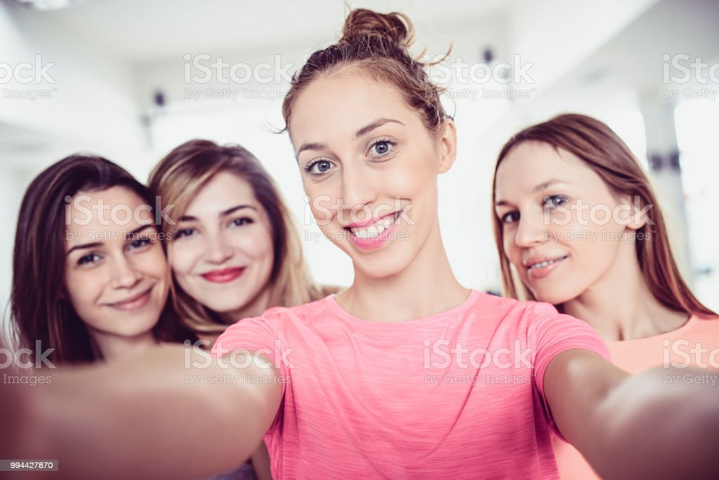 Portrait Of Cute Female Athletes Relaxing After Work Out Session In...