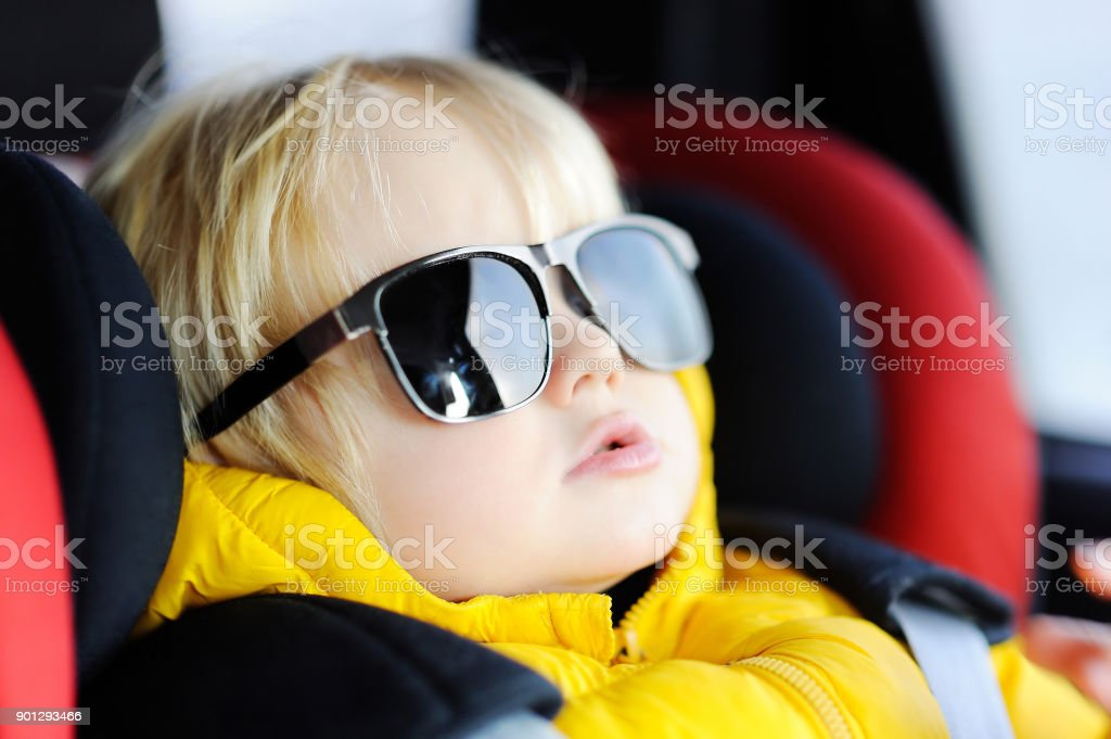 Portrait of cute funny little boy wearing father's sunglasses sitting in car seat stock photo