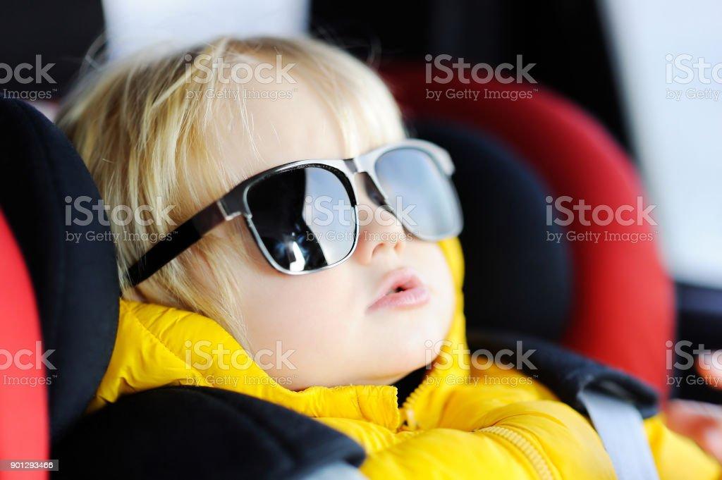 Retrato de niño pequeño divertido lindo llevando gafas de sol de padre sentado en el asiento de coche - foto de stock