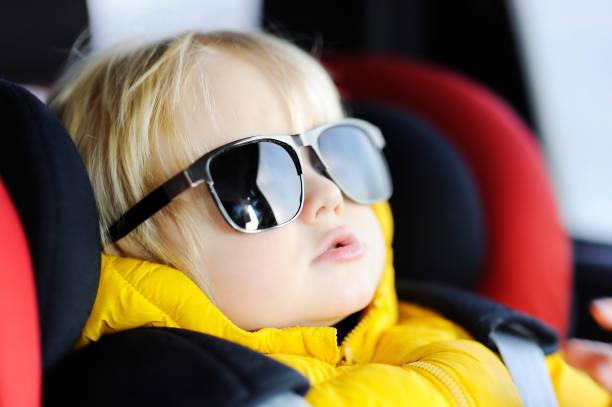 porträt von niedlichen lustigen kleinen jungen vaters sonnenbrille im kindersitz sitzen - sonnenbrille kleinkind stock-fotos und bilder