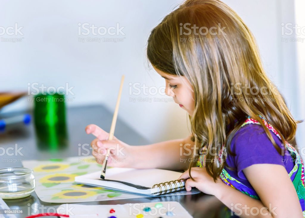 Portrait of cute girl concentrated while painting stock photo