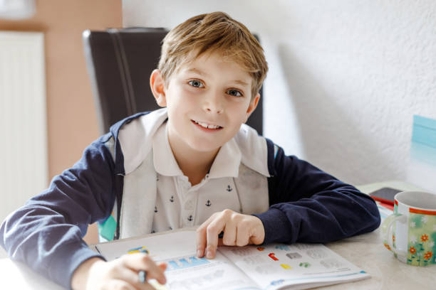 Portrait of cute happy school kid boy at home making homework. Little child writing with colorful pencils, indoors. Elementary school and education. Kid learning writing letters and numbers stock photo