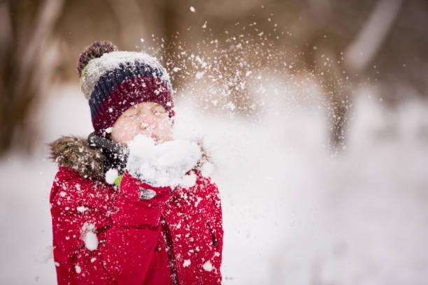 porträt von niedlichen kind junge schneetreiben aus seinen händen an einem wintertag. kinder spielen im freien. lifestyle-konzept - schneespiele stock-fotos und bilder