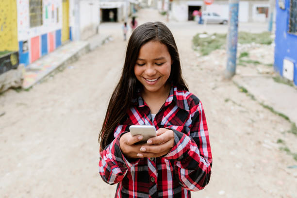 Portrait of cute latino girl using the mobile in shanty town. stock photo