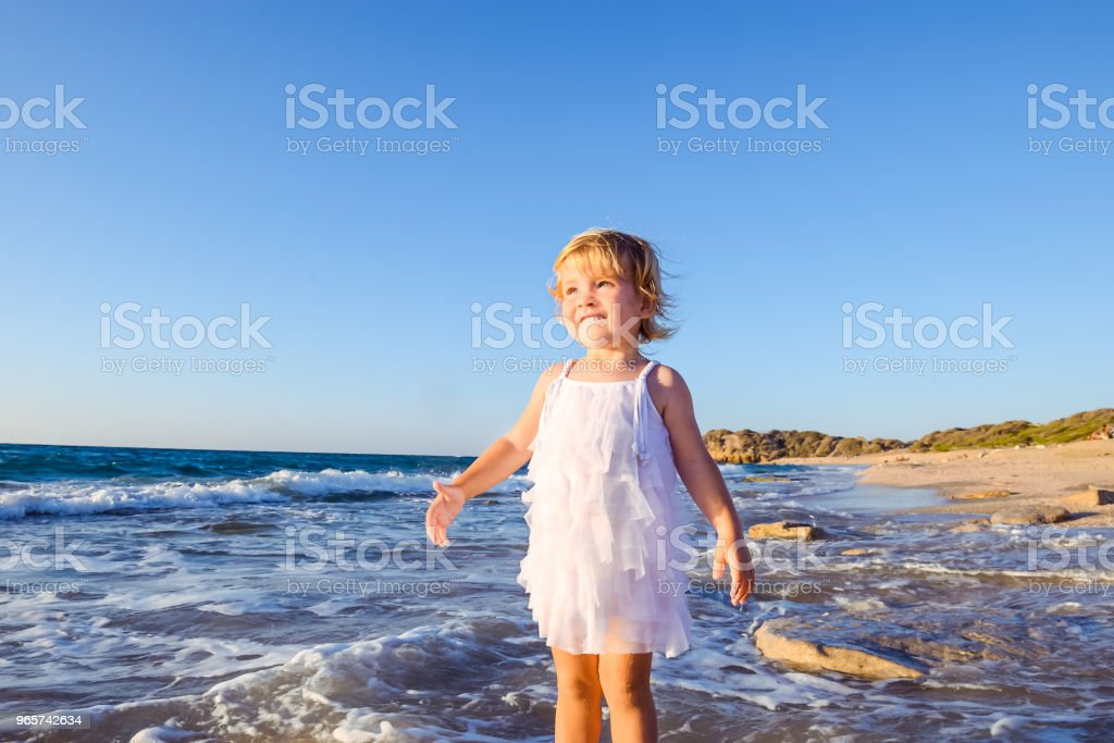 Portrait of cute little adorable toddler girl in white clothes walking on the empty beach on a warm sunny summer day. Holidays at sea. Family vacation. Selective focus, space for text. - Royalty-free Activity Stock Photo