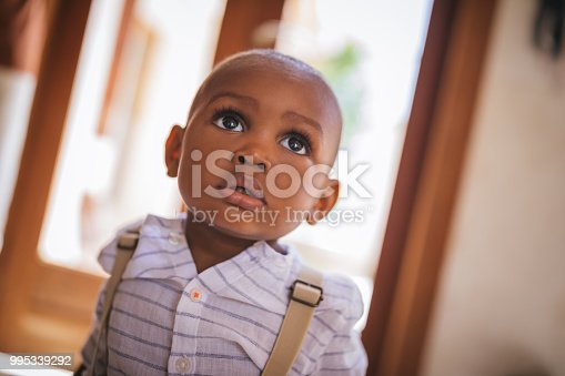 Portrait of adorable little African-American boy with big black eyes at home