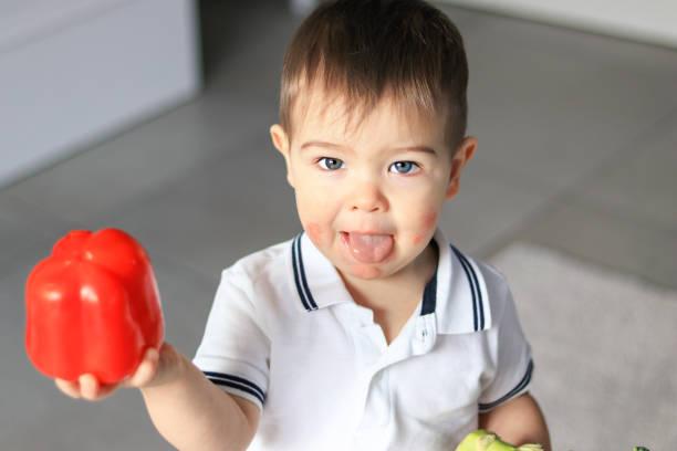 retrato de lindo bebé poco con su lengua hacia fuera con el dermatitis atópico en sus mejillas con pimiento rojo mostrando a la cámara. alergia alimentaria. - alergias alimentarias fotografías e imágenes de stock