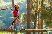 istock Portrait of cute little boy and girl walk on a rope bridge in an adventure rope park. 908639764