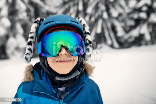 Little skier aged 9 is enjoying skiing on a winter day. The boy wearing cool helmet with ears is smiling into the camera.  Cold winter day. Nikon D850