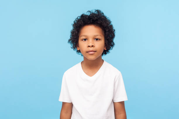 Portrait of cute little boy with stylish curly hairdo in white T-shirt standing, looking at camera with serious attentive face stock photo