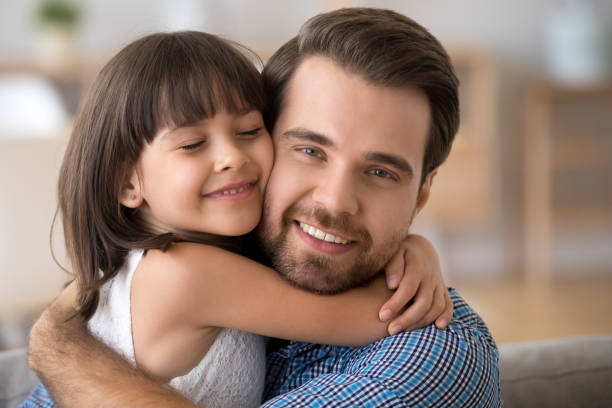 Portrait of cute little daughter hug young father Portrait of cute little daughter hold young happy father in arms show love and affection, adorable preschooler girl hug millennial dad, parent and small kid enjoy embrace cuddle at home young girls on webcam stock pictures, royalty-free photos & images