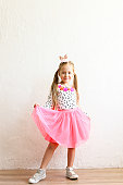 Portrait of cute little five year old girl with long blond hair wearing easter bunny ears on head, colorful polka dot shirt and pink tutu skirt. White wall backgroung, copy space, close up.