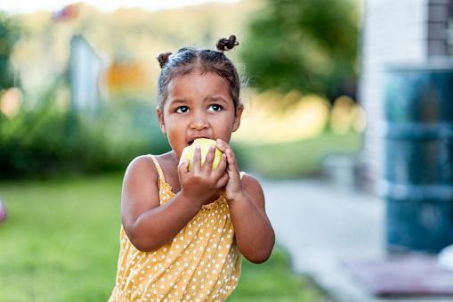Portrait of a cute little mixed race girl in a yellow summer rummper eating an apple.