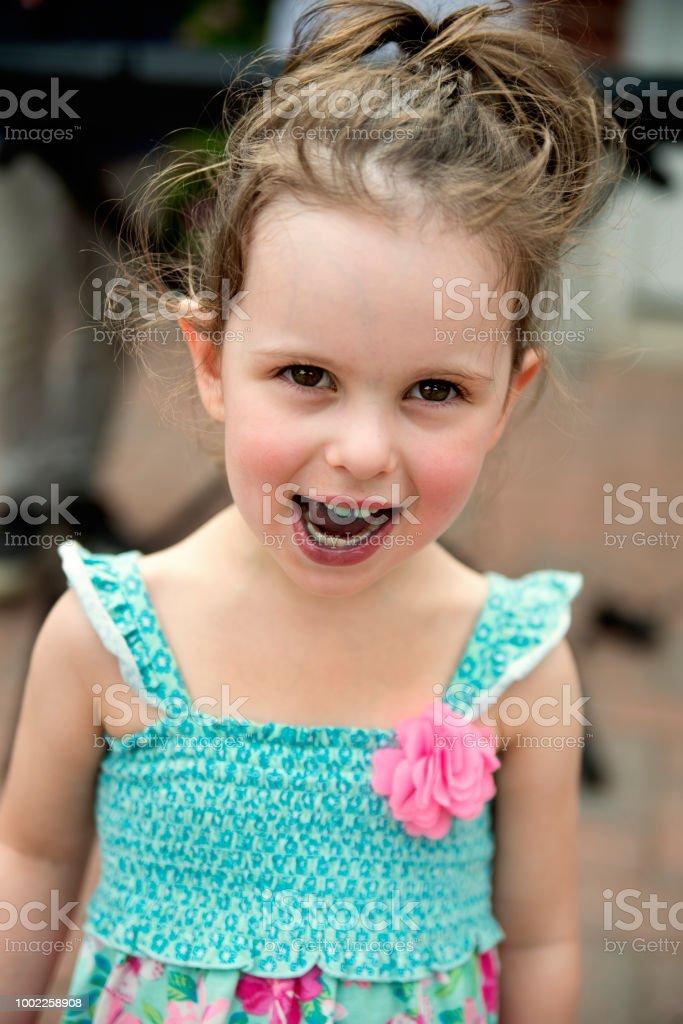 Portrait of cute little girl having eaten a blue candy outdoors in summer. stock photo