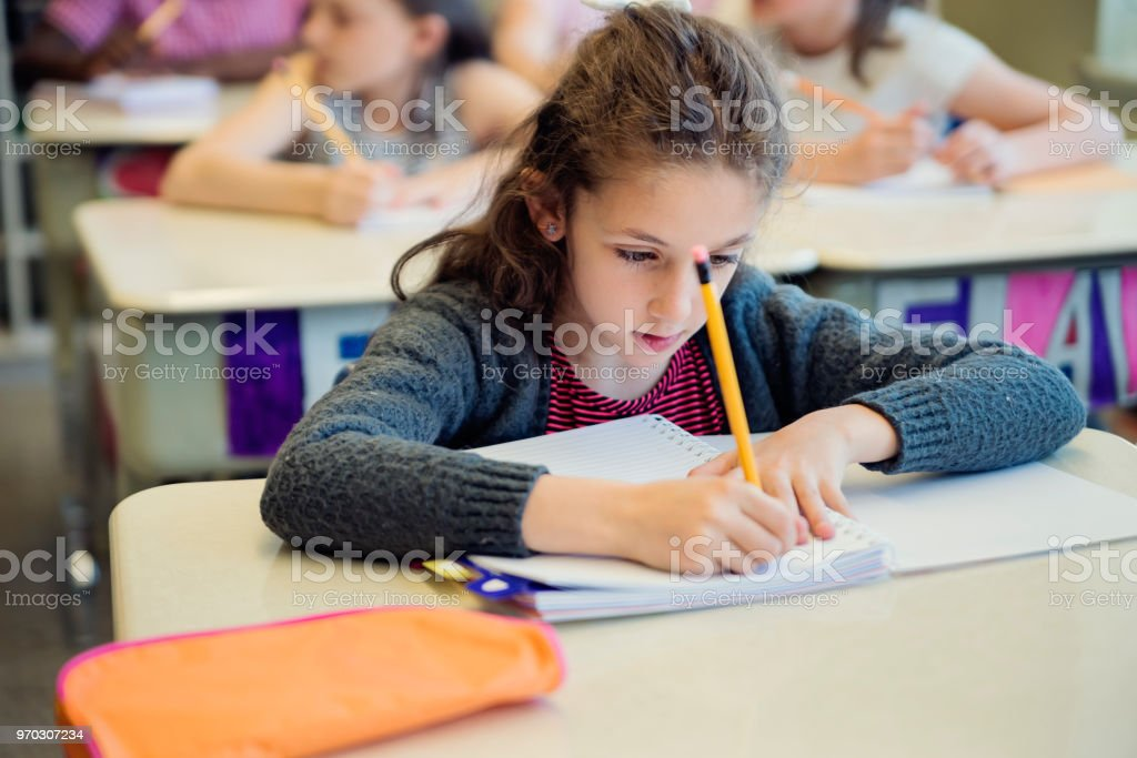 Portrait of cute little girl in classroom, working at her desk. royalty-free stock photo