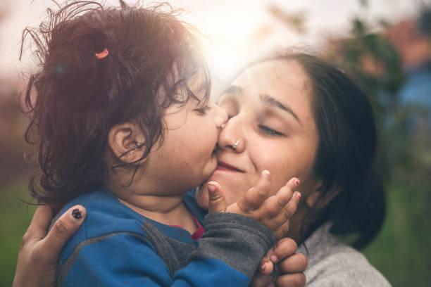 Porträt des niedlichen kleinen Mädchens küsst ihre Mutter – Foto