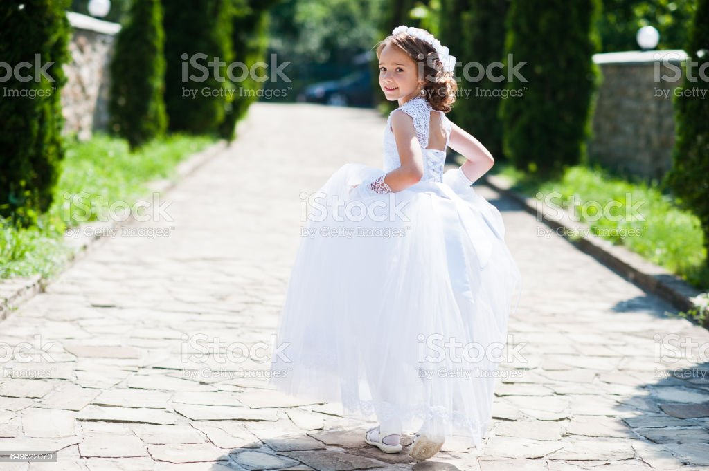 Portrait of cute little girl on white dress and wreath of first holy communion background thuja alley stock photo