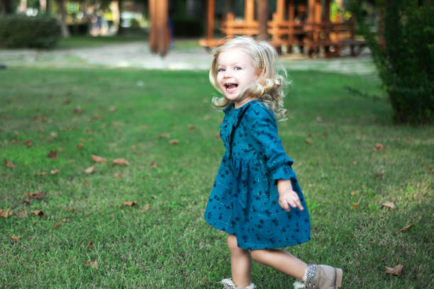 Portrait of cute little girl running by laughing in public park