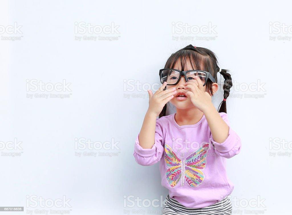 Porträt der niedliche kleine Mädchen, die versuchen, auf weißem Hintergrund eine Brille tragen. Lizenzfreies stock-foto