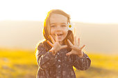 Portrait of cute little girl with flower in hair having fun in park or meadow on sunset.