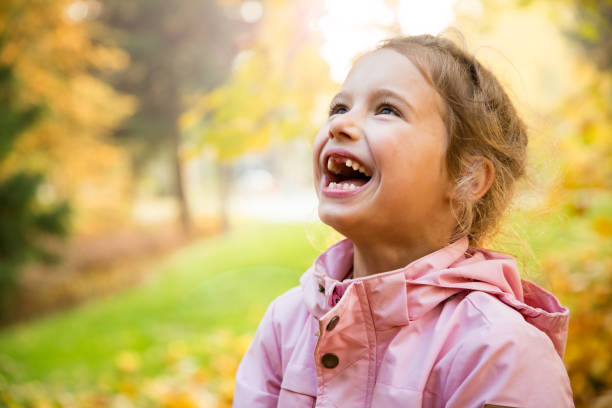 Portrait of Cute little girl with missing teeth playing with yellow fallen leaves in autumn forest stock photo