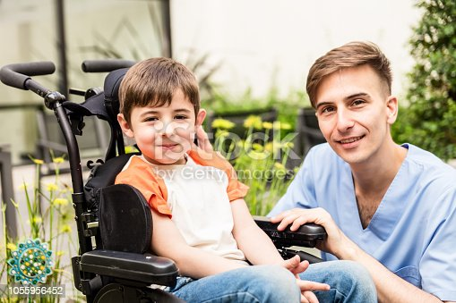 Portrait of cute little patient on wheelchair and nurse both smiling at camera very happy