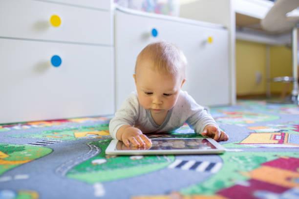 Retrato de lindo niño niño, jugar en tablet, niño sonriendo - foto de stock