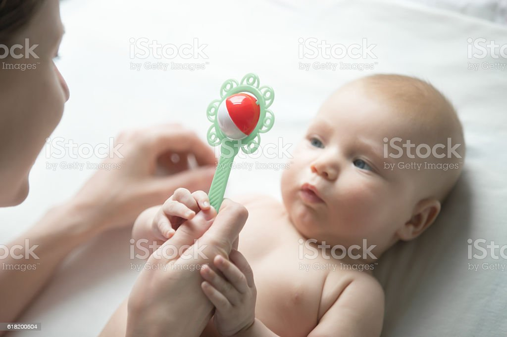 Portrait of cute newborn looking at mother hand with rattl stock photo