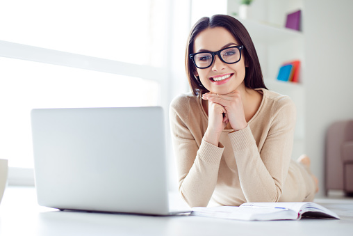 Portrait of cute nice-looking smiling businesswoman in glasses sitting at the table with laptop, notepad on it and holding up her head with hands