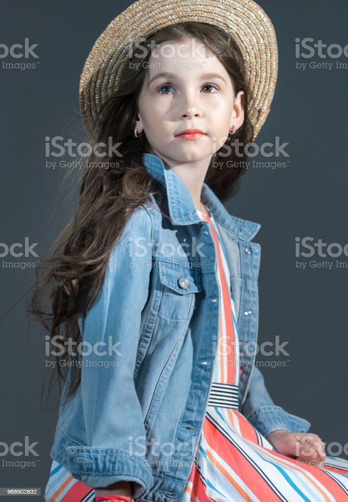 The lovely elementary age girl dressed in fashion casual clothing and...