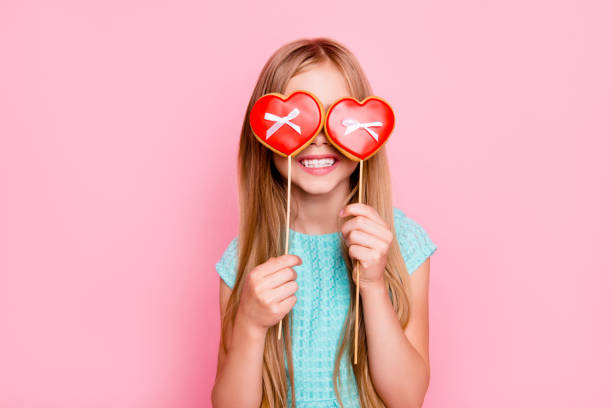 Portrait of cute playful dreamy with toothy smile beautiful girl fooling around, she is hiding her eyes behind cookies in shape of red heart with small bows, isolated on vivid pink background - foto stock