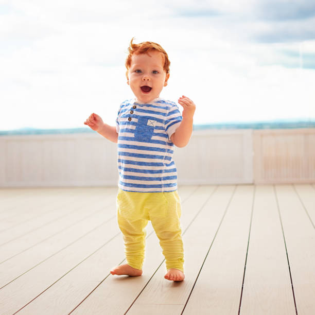 portrait of cute redhead, one year old baby boy walking on decking stock photo
