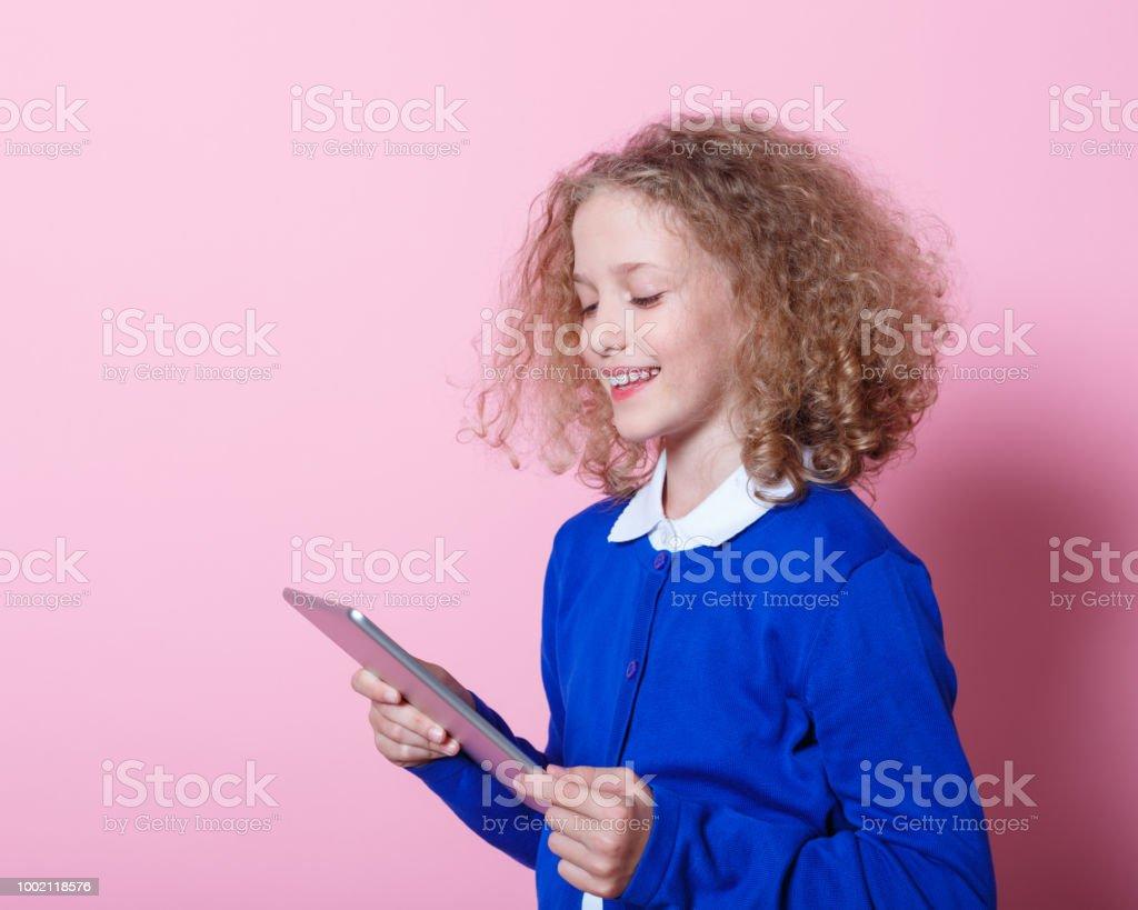 Portrait of cute schoolgirl using digtial tablet Happy schoolgirl wearing school uniforms using a digital tablet. Studio shot, pink background. 8-9 Years Stock Photo
