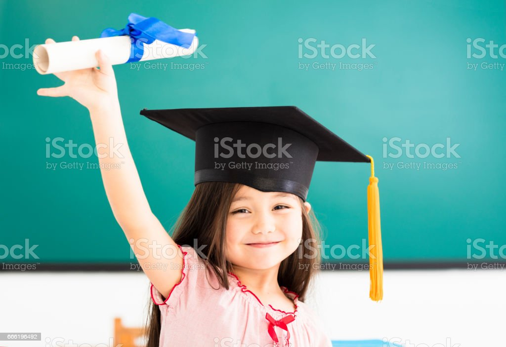 Portrait of  cute schoolgirl with graduation hat in classroom stock photo