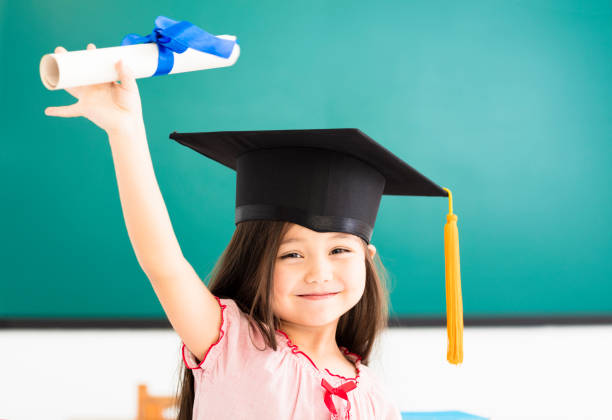 Portrait of  cute schoolgirl with graduation hat in classroom stock photo
