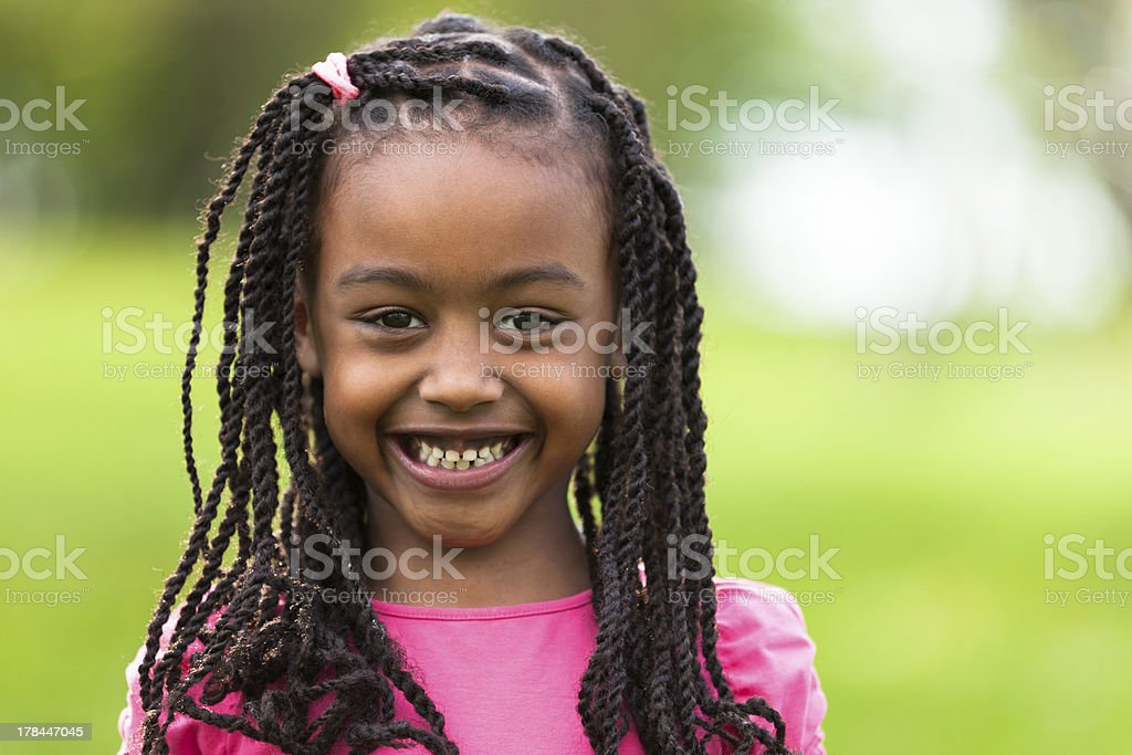 Portrait of cute smiling black girl in pink outdoors stock photo