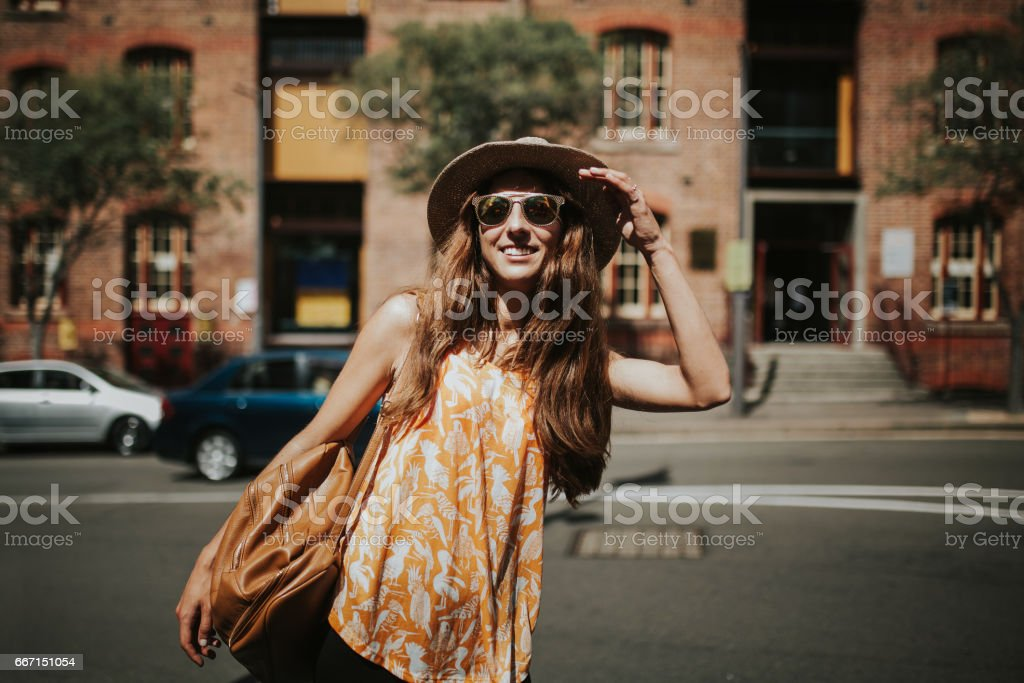 Portrait of cute smiling girl in sunglasses with city buildings in the background. stock photo