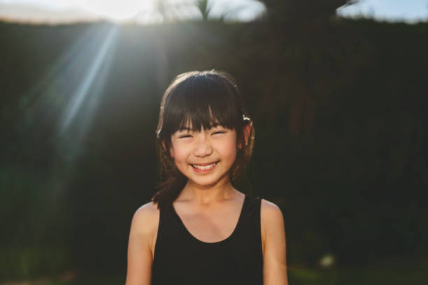 Portrait of cute smiling girl in yard on sunny day stock photo