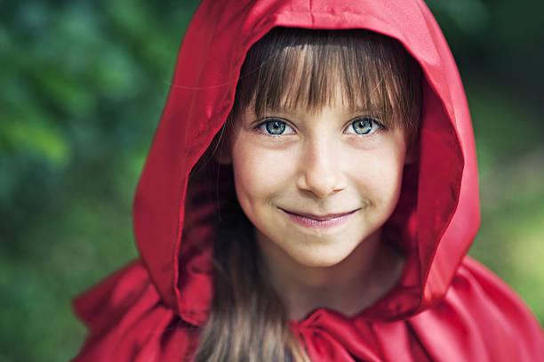 portrait of cute smiling little red riding hood - rotkäppchen kostüm stock-fotos und bilder
